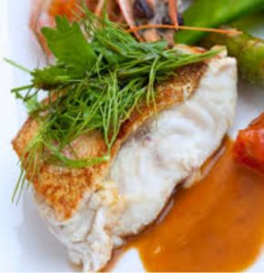 Baked cod fish topped with herbs and served with green beans and other vegetables